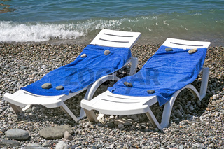 Two sun loungers for relaxing by the sea.