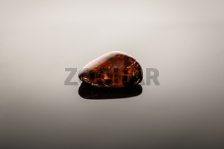 Piece of pietersite originating from Namibia Africa on glossy surface. Metamorphic gem stone type of tiger eye.