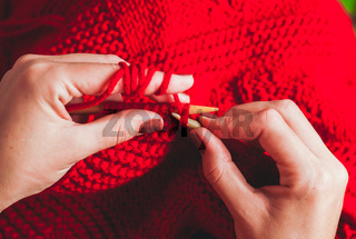 Female hands knits sweater