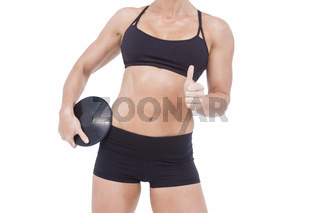 Female athlete holding discus and showing thumbs up