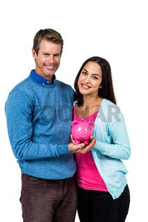 Portrait of couple holding piggy bank