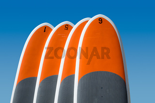 Four stand up paddle boards isolated against blue sky