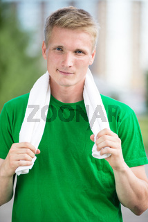 Tired man after fitness time and exercising. With white towel