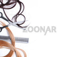 Scissors and comb with brown and blond hair isolated left