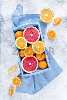Fresh fruits citruses on a rustic white background. Raw and vegetarian eating frame. Sliced tangerines, oranges, grapefruits, blue tray.