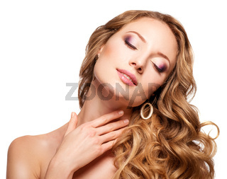 Beautiful woman with long wavy hair touching her neck