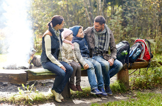 happy family sitting on bench and talking at camp