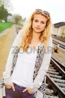 Junge Frau im Hippie-Look steht am Bahnhof