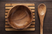 wooden salad plate and spoon on brown table