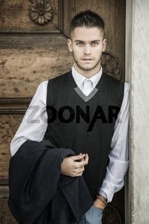 Handsome young man against old wood door