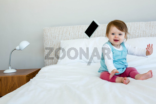 adorable baby giggling and throwing a phone