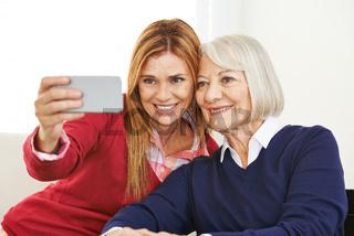 Junge und alte Frau machen zusammen Selfie