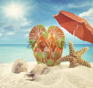 Sandals and starfish with beach umbrella at the ocean