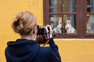 Frau fotografiert ein Fenster mit kleinen Hundefiguren