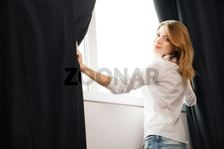 Girl opens the curtains and relaxing in morning