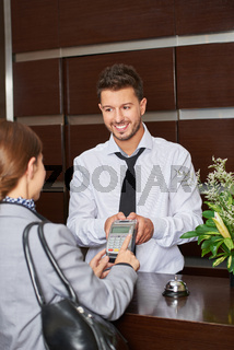 Frau bezahlt mit Kreditkarte beim Concierge