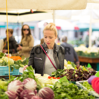 Woman buying vegetable at local food market.