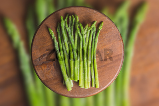 Frozen sticks of asparagus on rustic blurred wood and vegetable background. horizontal view.