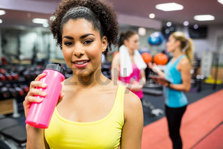 Fit woman smiling at camera in weights room