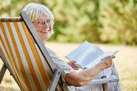 Alte Frau mit Buch lacht glücklich