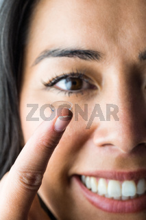 Smiling woman with a contact lens