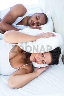 Disturbed wife sleeping besides snoring husband
