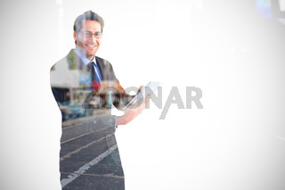 Composite image of businessman looking at the camera while using his tablet