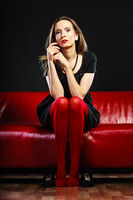 Fashion woman in red pantyhose on couch