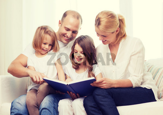 smiling family and two little girls with book