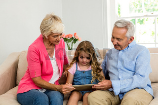 Happy grandparents and girl using digital tablet