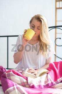 blonde frau sitzt mit kaffee und buch im bett
