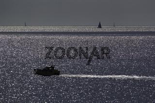 Motorboot auf dem Meer bei glitzernden Wasser und Gegenlicht