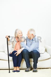 zwei Senioren kuscheln auf dem Sofa