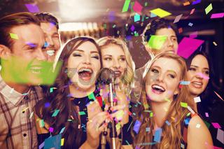 Composite image of happy friends singing karaoke together