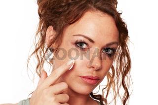 Frau mit natuerlicher Haut traegt eine Gesichtscreme auf