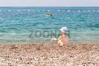 Little boy play near sea