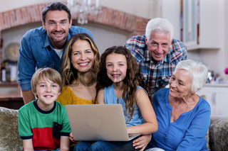 Multi-generation family sitting on sofa and using laptop