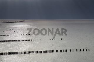 Buhnen in der Ostsee bei dunklen Wolken und glitzernden Wasser am Meer