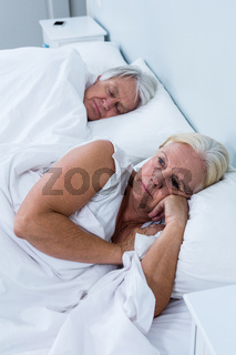 Thoughtful senior woman lying on bed