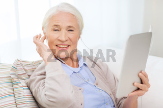 senior woman with tablet pc and earphones at home