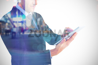 Composite image of mid section of a businessman using digital tablet