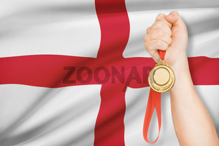 Sportsman holding gold medal with flag on background - England
