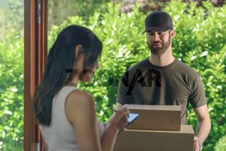 Frau quittiert den Empfang von zwei Paketen