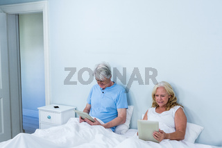 Retired couple using digital tablets while sitting on bed