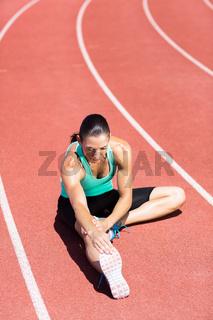 Female athlete stretching her hamstring