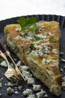 Ein Stück Börek mit Fetakäse und Petersilie