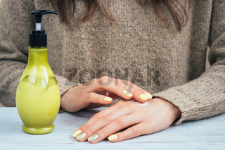 Women's hands with yellow manicure applied the cream for hands