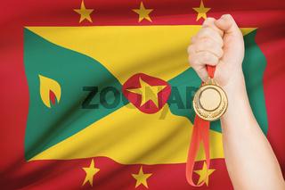 Sportsman holding gold medal with flag on background - Grenada
