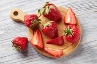 Slices and whole ripe strawberries on a wooden board on a gray wooden background. Healthy vtamin berry. Flat lay