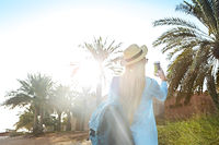 Tourist woman in hat taking photo of the old part of Dubai using mobile smartphone